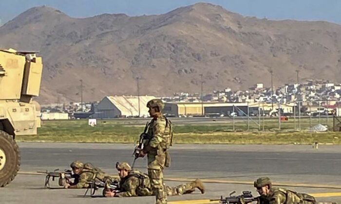 US soldiers take up their positions as they secure the airport in Kabul on August 16, 2021, after a stunningly swift end to Afghanistan's 20-year war, as thousands of people mobbed the city's airport trying to flee the group's feared hardline brand of Islamist rule. (Photo by SHAKIB RAHMANI / AFP) (Photo by SHAKIB RAHMANI/AFP via Getty Images)